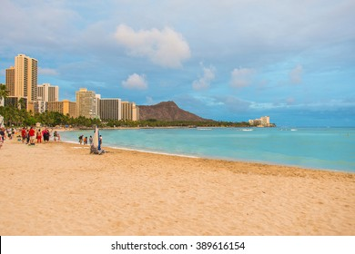 Peaceful Waikiki beach on the island of Oahu, Hawaii during sunset with a Honolulu city and Diamond head crater on the background.