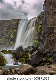 Peaceful waterfall in Tingvellir, Iceland, pouring down on the tectonic plate