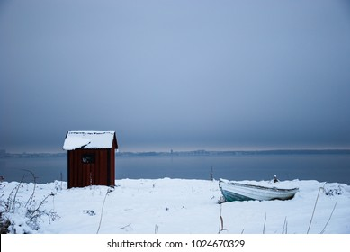Peaceful winter view with old fishing cabin and boat by the coast of the swedish island Oland in the Baltic Sea