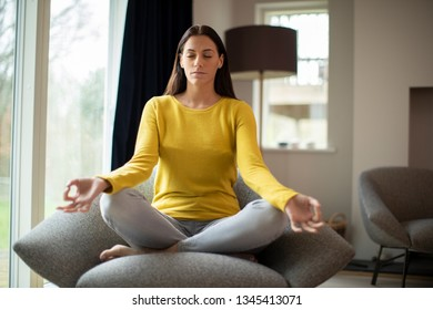 Peaceful Woman Meditating Sitting In Chair At Home