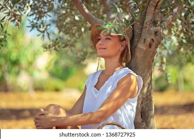 Peaceful woman with pleasure resting in the olive garden, nice farmer girl enjoying freshness of a spring nature, happy life in a countryside