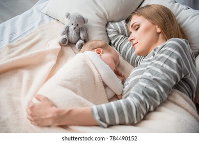 Peaceful woman slumbering with lovely little daughter on comfortable sheets. She is hugging baby with tenderness