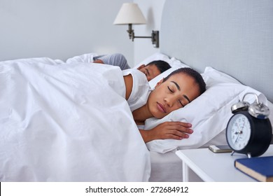 peaceful young couple sleeping comfortably in bed at home
