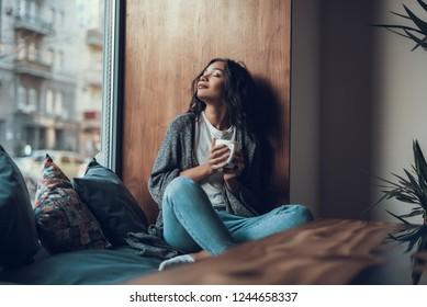 Peaceful young lady sitting on the window sill and smiling while drinking tea with her eyes closed - Shutterstock ID 1244658337