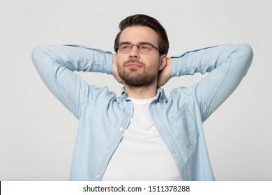 Peaceful young man in eyeglasses folding hands behind head, stretching back head shot studio portrait. Mindful calm relaxing, resting, visualizing planning future isolated on grey white background.