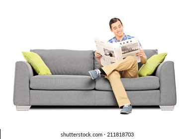 Peaceful young man reading the news seated on sofa isolated on white background