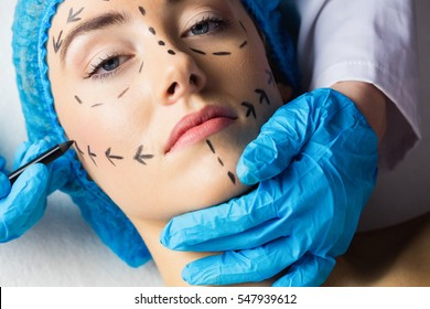 Peaceful young patient with dotted lines on the face in an examination room