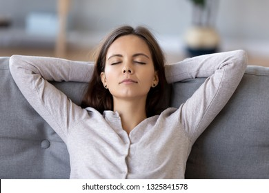 Peaceful young woman with hands behind head relaxing at home, sitting on comfortable sofa in living room, carefree girl with closed eyes resting, daydreaming, thinking about good future