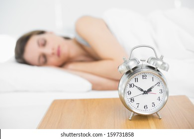 Peaceful young woman lying under the cover on her bed sleeping