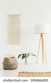 Peaceful zen living room interior with jute decorations, tripod floor lamp and a beige macrame on a white wall