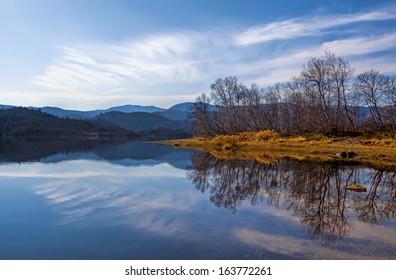 Peacefull lake, bare trees and autumn colors at Haukeli, Norway