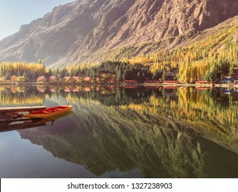 Peacefully lower Kachura lake in autumn. A view of docked boat on still water and foliage with mountain in the background. Skardu, Gilgit Baltistan, Pakistan.