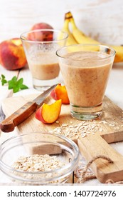 peach banana smoothie with oatmeal  in a glass,  fresh peaches on a wooden background