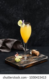 Peach champagne Bellini cocktail decorated with orchid flower on wooden board. Traditional italian alcoholic drink