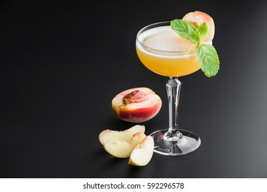 """peach champagne cocktail """"bellini""""  on a dark uniform background with mint"""