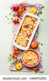 Peach cobbler preparation. Fresh whole and halves of peaches and baking pan with peach crumble and shortbread dough on light background, top view