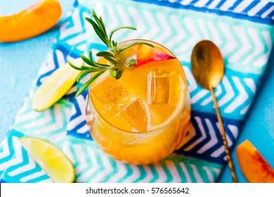 Peach cocktail, fizz, ice tea with fresh rosemary and lime. Blue background.