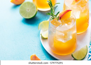 Peach cocktail, fizz, ice tea with fresh rosemary and lime. Blue background. Copy space.