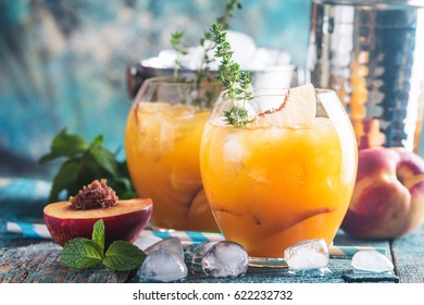 Peach cocktail or tea with ice and thyme on blue background.