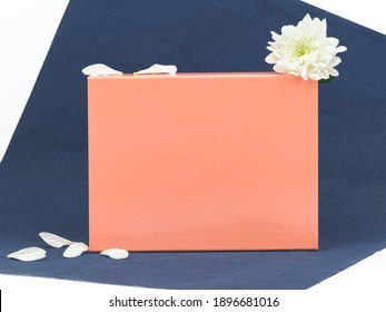 Peach color cardboard gift box mock up decorated with white flower and petals on dark blue background. Copy space, branding concept
