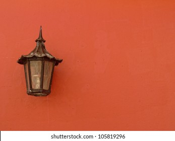 Peach colored colonial wall with old street lamp on an old architectural restored building in old san juan puerto rico