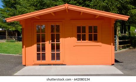 Peach coloured wooden summerhouse in sunlight.