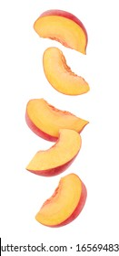 Peach fruit pieces in the air. Five slices of fresh peach falling over white background