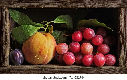 Peach and grape in wooden box. Imitation of antique painting.