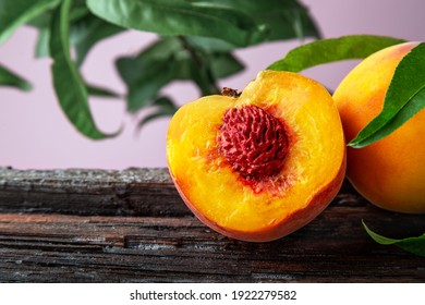 Peach in halves with bone. Peaches with leaves on wooden board. Ripe juicy peaches. Harvest of peaches for food. Fresh organic fruit on pink background with copy space