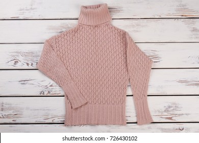 Peach handmade sweater on wooden showcase. Knitted pullover with roll neck and long sleeves. Beautiful crochet pattern.