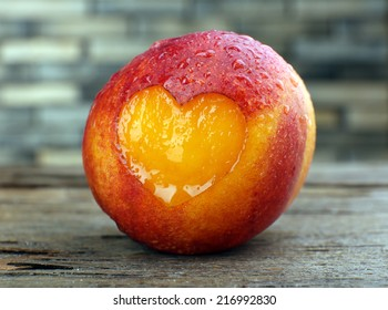Peach with heart on wooden table, close-up