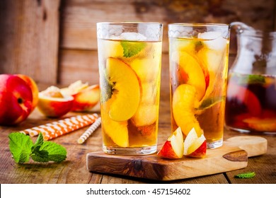 Peach ice tea in a glass with mint on wooden table