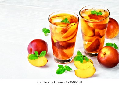 Peach ice tea in a glass with mint on a white wooden table(selective focus).