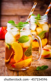 Peach ice tea in mason jar with mint on wooden table