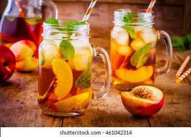 Peach ice tea in mason jar with mint on wooden table