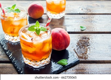 Peach iced tea. Iced tea with peach slices, mint and ice cubes close up. Homemade refreshing summer drink.