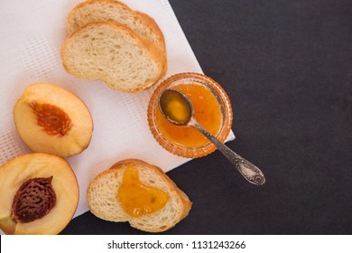 peach jam with toast on a white napkin that lies on a black background, Flatline with peach jam spoon and toas