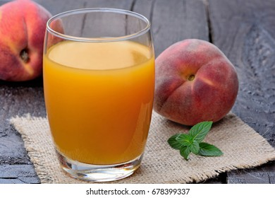 Peach juice in a glass on wooden table close-up
