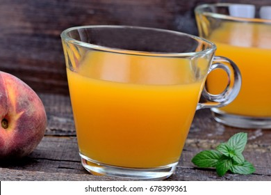 Peach juice in a glasses on wooden background close-up
