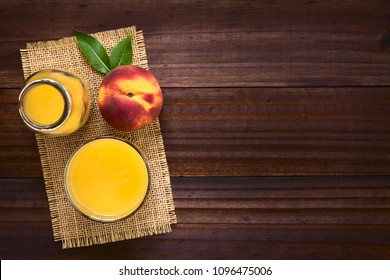 Peach juice or nectar with fresh ripe peach fruit on the side, photographed overhead on dark wood with natural light (Selective Focus, Focus on the top of the juice and the top of the whole fruit)