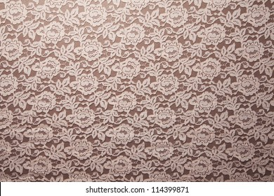 Peach lace sits on a brown background.
