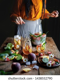 Peach lemonade with strawberries, limes, summer lemonade with ice on the black dark rustic background. Women pours lemonade to the glass, splash of lemonade
