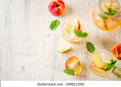 Peach and lime lemonade, mojito cocktail with fresh fruit garnish, om light concrete background copy space selective focus