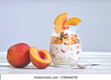 Peach parfait sweet tasty dessert in the glass made from ice-cream, almond nuts and peach fruits. Delicious beautiful food