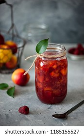 Peach and raspberry jam in a glass jar. The ingredients of the concrete background.