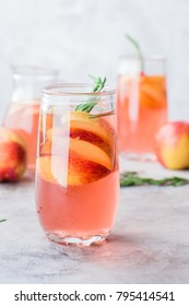 Peach and rosemary lemonade, cocktail on a gray stone concrete table background. Summer drink.