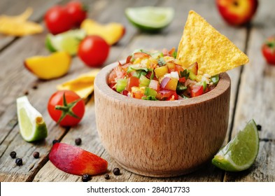 peach salsa on a dark wood background. the toning. selective focus