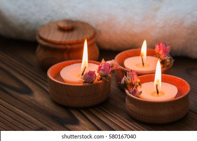Peach small candles in wooden cups with dried flowers