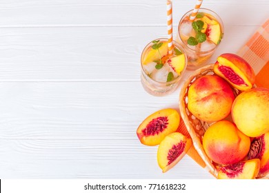 Peach summer cocktail or lemonade with ice and mint leaves. Cold refreshment organic non-alcohol drink with ripe nectarine fruit on wooden background.