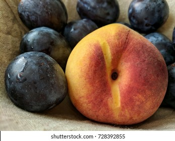 peach surrounded by plums in fruit basket